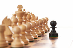 Black pawn challenging army of white chess pieces. Selective focus royalty free stock photography