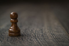 Black Pawn, Chess Piece on a Wooden Table Royalty Free Stock Image