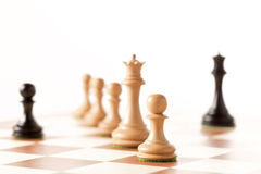 Black pawn on a chessboard with white chess pieces Royalty Free Stock Photos