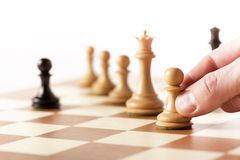 Black pawn on a chessboard with white chess pieces Stock Images