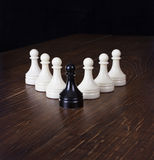 Black pawn in focus on a background white pawns. Stock Photos
