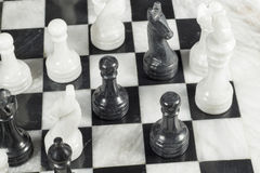 Black pawn gives checkmate to white king. Marble chess board Royalty Free Stock Photo