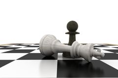 Black pawn standing over fallen white king Royalty Free Stock Photo