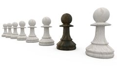 Black pawn standing with white pawns Stock Photo