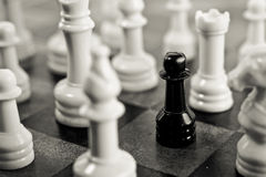 Black Pawn Trapped. Black pawn surrounded on chess board by white pieces in black and white Stock Photo