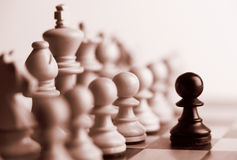 Black pawn and white chess pieces. Sepia tone royalty free stock photos