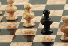 Black pawn between white pawns Stock Images
