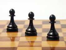 Black pawns. Three black pawns set diagonally royalty free stock images