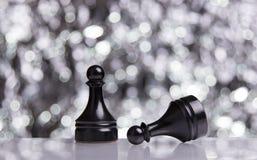 Black Pawns on festive bokeh background Stock Photo