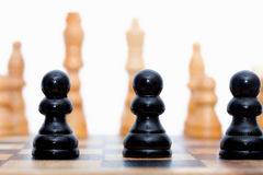 Black pawns lined up Royalty Free Stock Images