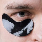 Black pearl extract. Skin care. Minimizes puffiness and reduce dark circles. Eye patches for men. Man with black eye. Patches close up. Metrosexual concept stock photo