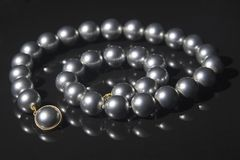 Black pearls necklace. Over black background royalty free stock photo