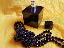 Black pearls necklale with perfume bottle on yellow background. Elegant Royalty Free Stock Images