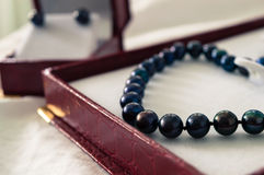 Black pearls. A black pearl necklace in a red jewelry box Stock Photo