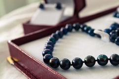 Black pearls. A black pearl necklace in a red jewelry box Royalty Free Stock Photos