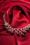 Black pearls on red textile. Black pearl necklace on red textile Stock Photo