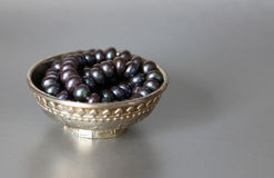 Black pearls in a silver cup Stock Image