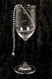 Black pearls in wine glass. A string of black pearls hanging over the edge of a crystal wine glass, on black velvet Stock Photo