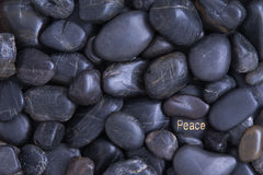 Black pebble background with a Peace theme Royalty Free Stock Image