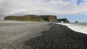 Black pebble beach in Iceland. Promontory of Dyrholaey and rock arch Lundadrangur from a nearby black pebble beach stock photos