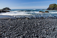 Black pebble beach on pacific coast Royalty Free Stock Photo
