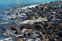 Black pebble beach Stock Images