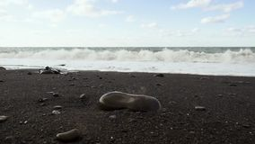 Black pebble sandy shore and foam waves slow motion. Black pebble sandy shore and foam waves with rolling waves under a cloudy bright sky slow motion stock video footage