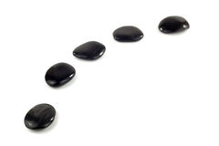 Black pebbles in a curved line Stock Photo