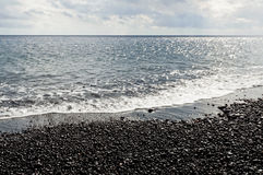 Black pebbles and sea Stock Images