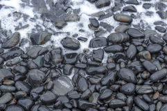 Black Pebbles with wave on Sea Beach Royalty Free Stock Photo