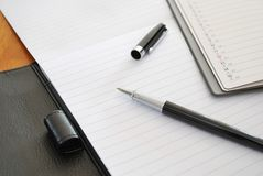 Black pen on blank writing pad. Or planner signifying concepts such as office and business, and work related objects Stock Photography