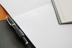 Black pen with blank writing pad. And planner signifying concepts such as office and business, and work related objects Stock Photo