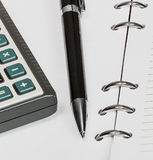 Black pen and calculator, notebook. Black pen and calculator on a white sheet of notebook Stock Photography
