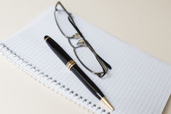 Black pen and glasses with white pad or notepad Stock Photos