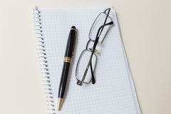 Black pen and glasses with white pad or notepad Royalty Free Stock Photos