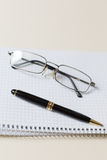 Black pen and glasses with white pad or notepad Royalty Free Stock Images