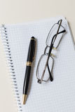 Black pen and glasses with white pad or notepad Royalty Free Stock Photo