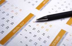 Black pen lying on the calendar. Close-up Stock Images