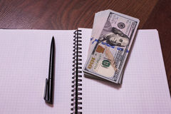 Black pen, note book page and money Stock Photography