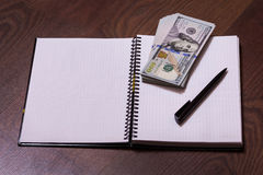 Black pen, note book page and money Royalty Free Stock Photography