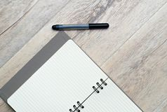 Black pen and note pad diary. Pen and note pad,  on wooden texture. Business concept Royalty Free Stock Images