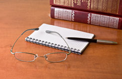 Black pen with notebook and glasses Stock Photos