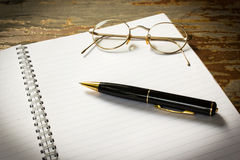 A black pen on an open book with glass. Stock Photo