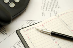 Black pen on planner. With business documents in background, signifying concepts such as office and business, planning for the new year, financial budget and Royalty Free Stock Image