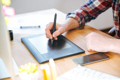 Black pen tablet with stylus used by male designer hand Royalty Free Stock Image