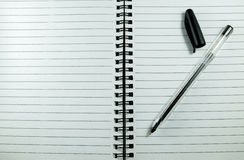 Black pen on white notebook Royalty Free Stock Photography