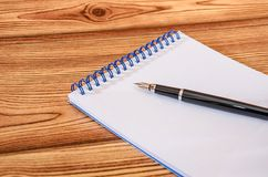 Black pen on white notepad against the background of a wooden table. Close-up. royalty free stock photos