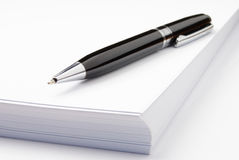 Black pen and white paper. Black ballpoint pen and sheets of white paper Royalty Free Stock Images