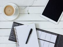 Black Pen on White Writing Spring Notebook Between White Ipad and White Ceramic Mug With Latte on White Plate Royalty Free Stock Image