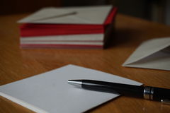Black pen writing announcement letter with the envelope on the wooden desk Stock Images